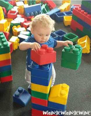 Small toddler builds something with big bricks