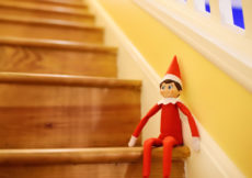 Funny Christmas toy elf on stairs