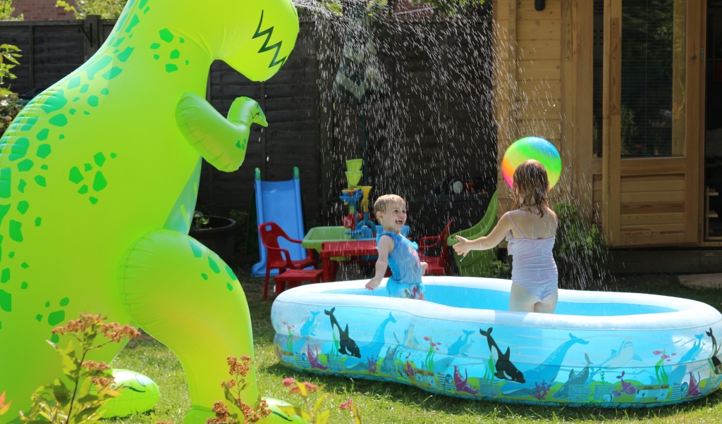 Playing in the garden with a huge dinosaur sprinkler