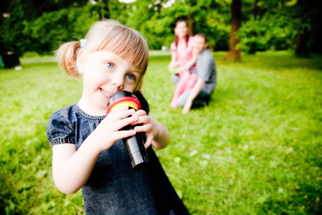 Little Girl With Microphone In Hand. Close-Up Portrait