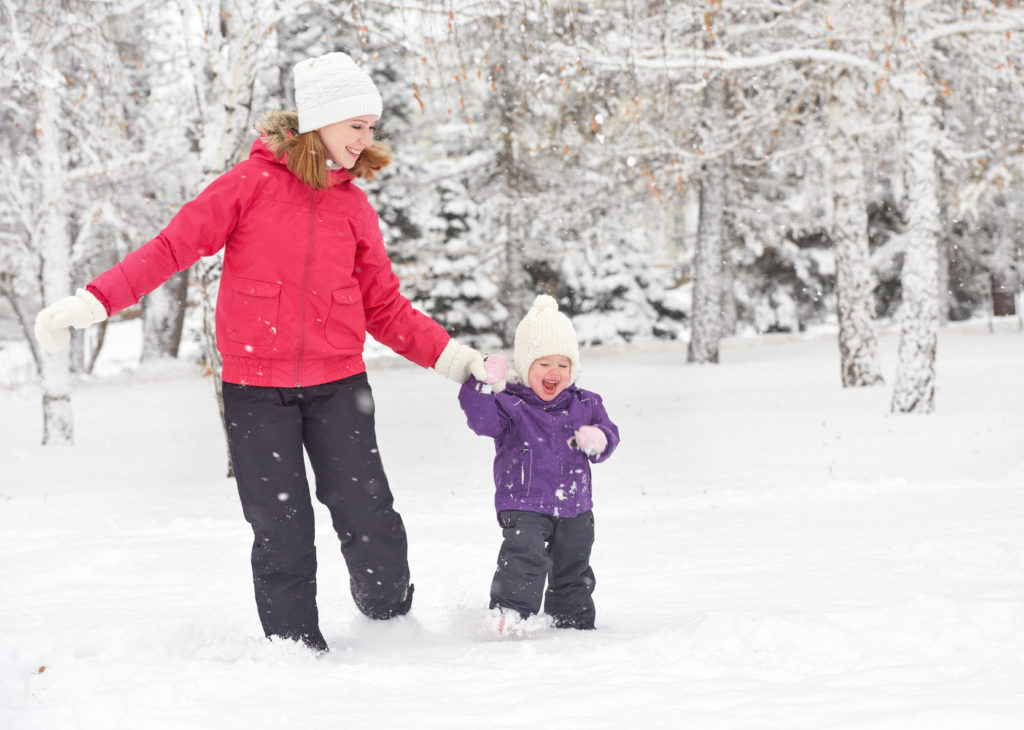 happy family mother and baby girl daughterтrun, walk playing  in winter outdoors in the snow