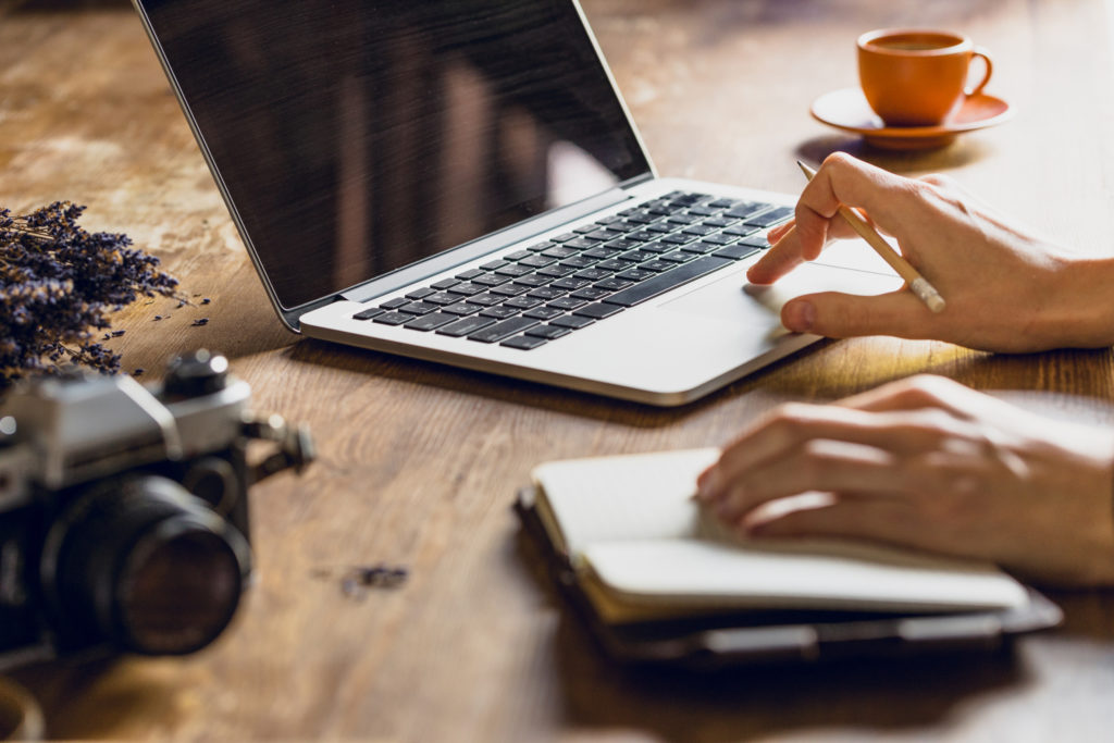 person using laptop and diary at workspace with vintage photo camera