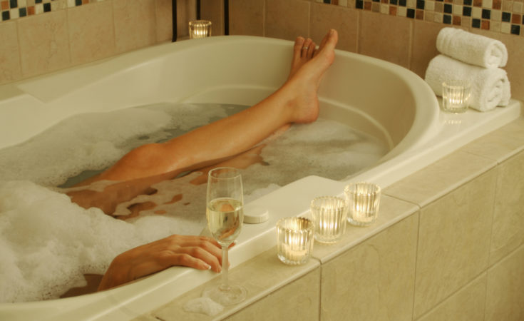 Beautiful Woman in bubble bath with sparkling wine and candles surrounding her.
