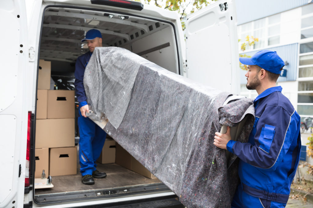 Two Young Delivery Men In Uniform Unloading Furniture From Vehicle moving house removals